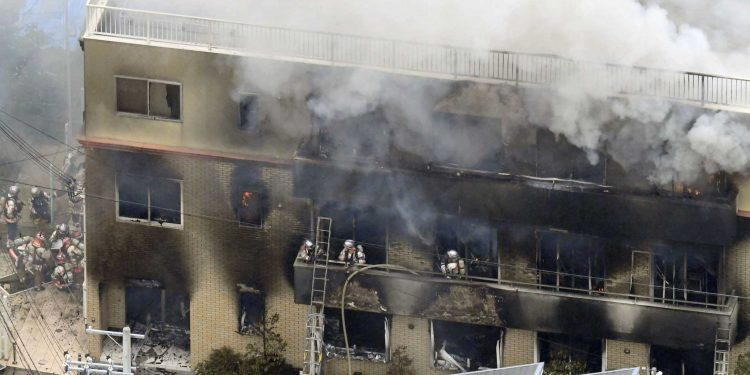 Firefighters respond to a building fire of Kyoto Animation in Kyoto, western Japan, Thursday, July 18, 2019. The fire broke out in the three-story building in Japan's ancient capital of Kyoto, after a suspect sprayed an unidentified liquid to accelerate the blaze, Kyoto prefectural police and fire department officials said.(Kyodo News via AP)